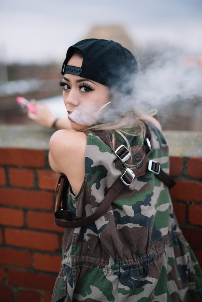 woman vaping with camo top